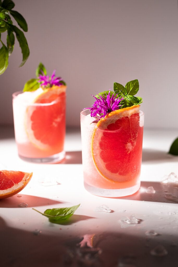 two glasses with grapefruit slices, pink flowers, and basil leaves.