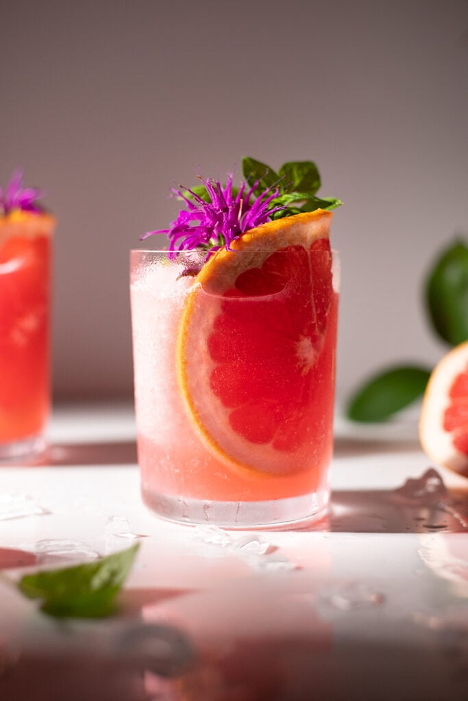 close up of a pink frozen drink with grapefruit slice, flower, and basil leaves.