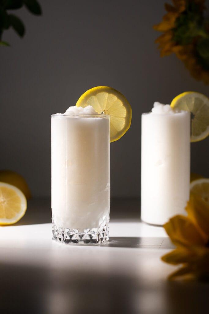 two glasses of frozen whipped lemonade with lemon wheels.