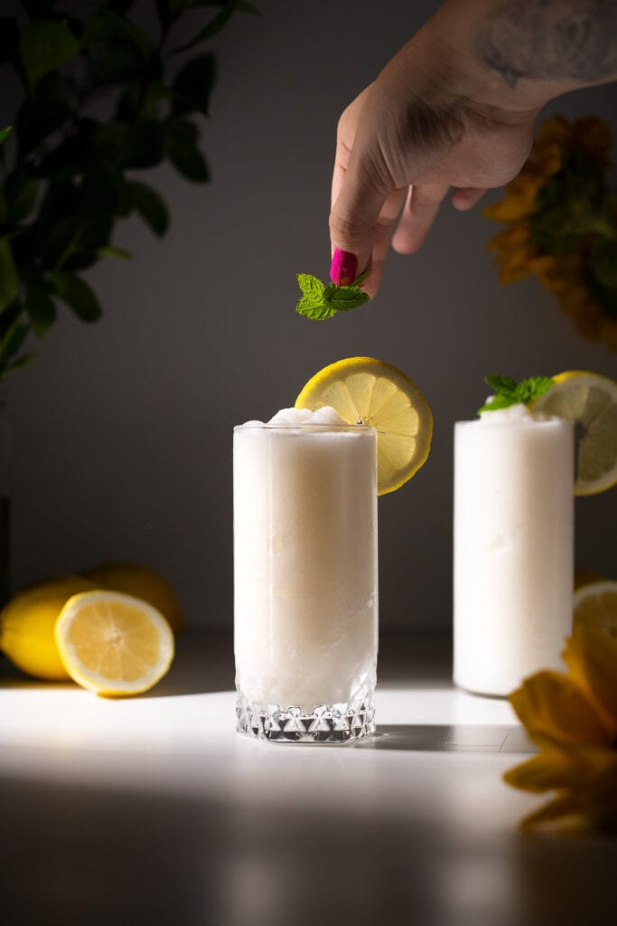 a hand adding a mint sprig to a frozen drink.
