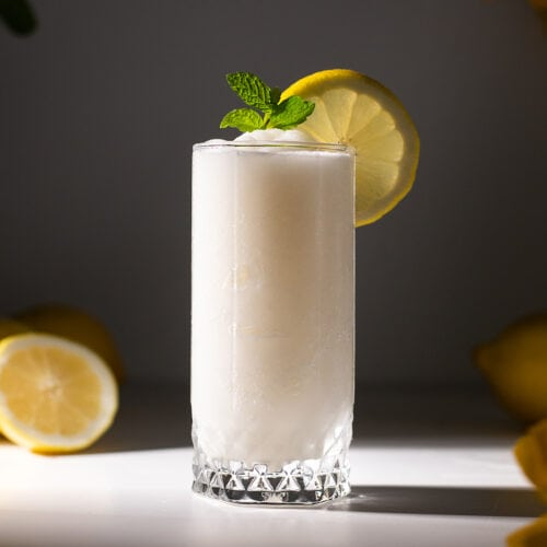 a tall glass filled with white frozen lemonade.
