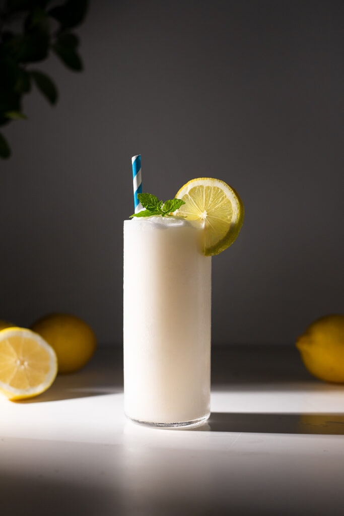 a glass of whipped lemonade with a blue paper straw.