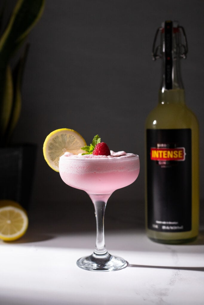 a glass filled with a frothy pink drink next to a bottle of Barrow's Intense Ginger Liqueur.