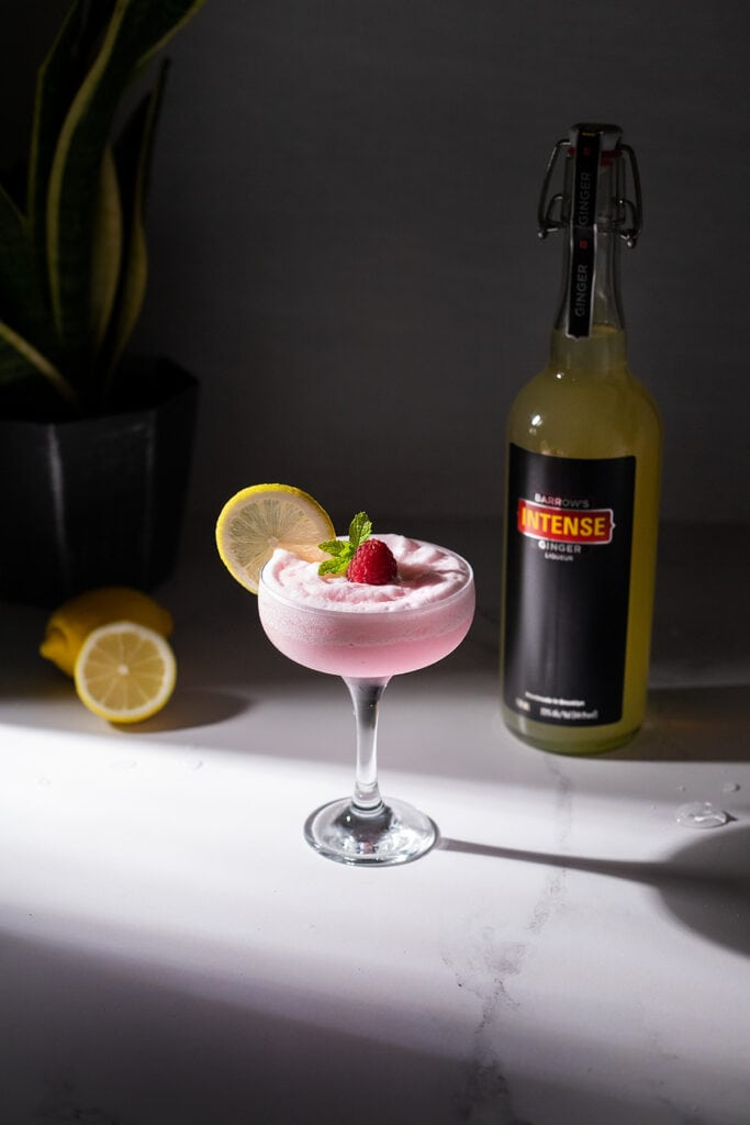 a marble table with a pink cocktail, liquor bottle, lemons and a plant.
