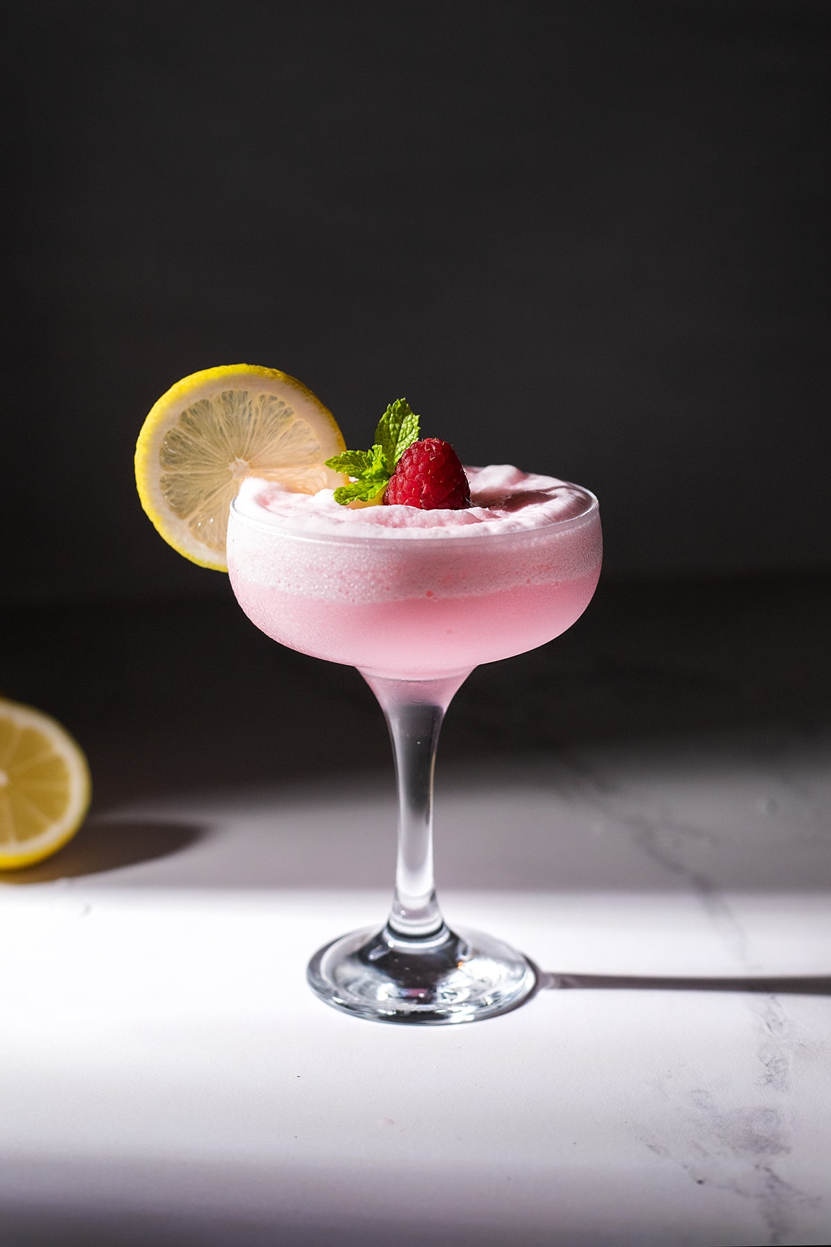 a large coupe glass filled with frozen pink lemonade.