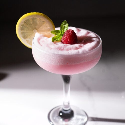 a coupe glass filled with a pink drink with a lemon wheel.
