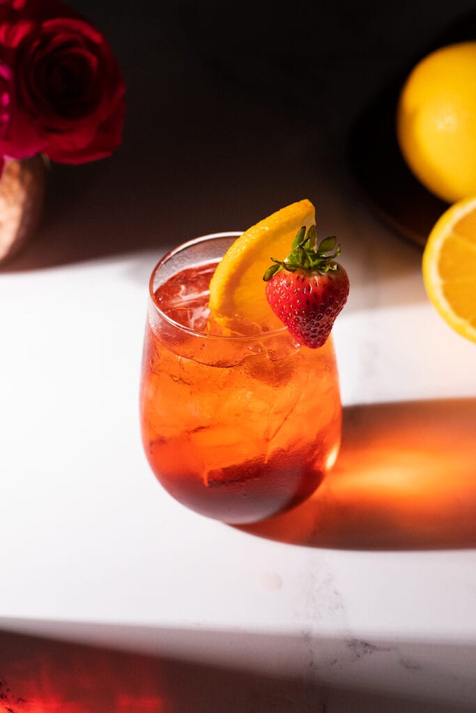 a bright red drink in a stemless wine glass with a strawberry and orange slice.