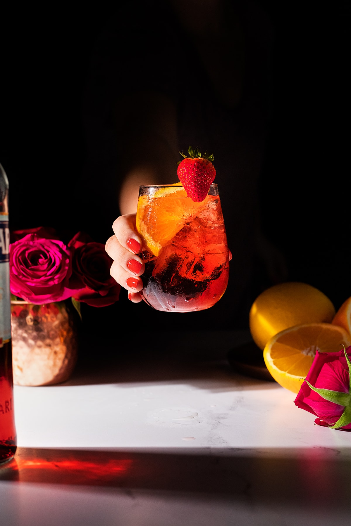 a hand with bright red nails holding a stemless wine glass filled with a red cocktail.