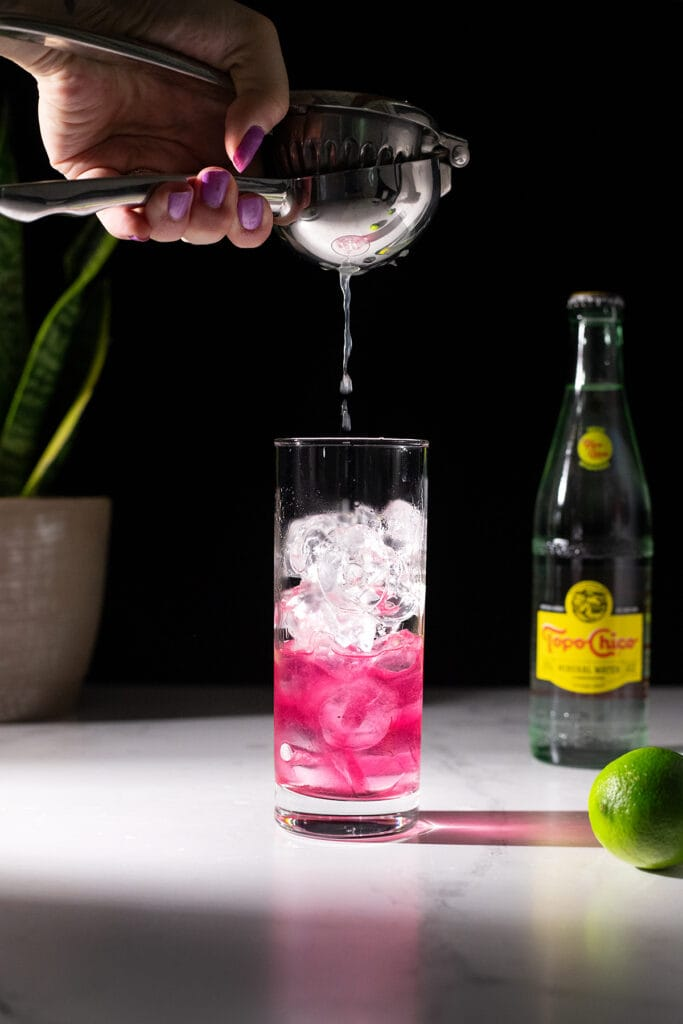 squeezing a lime into a highball glass.
