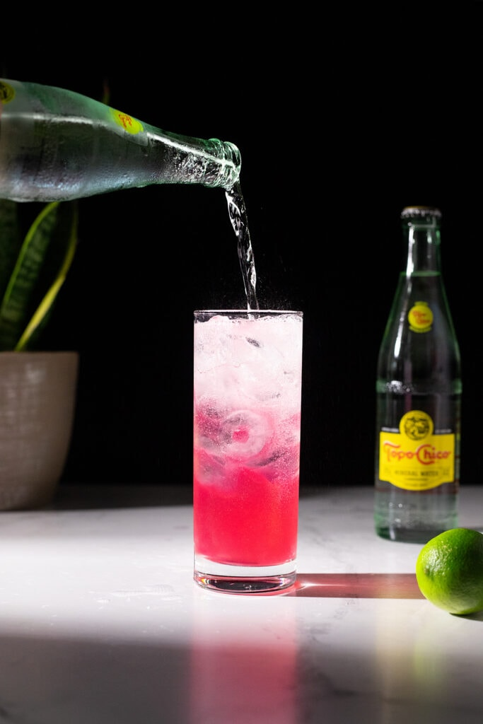 pouring Topo Chico Mineral Water into a highball glass.