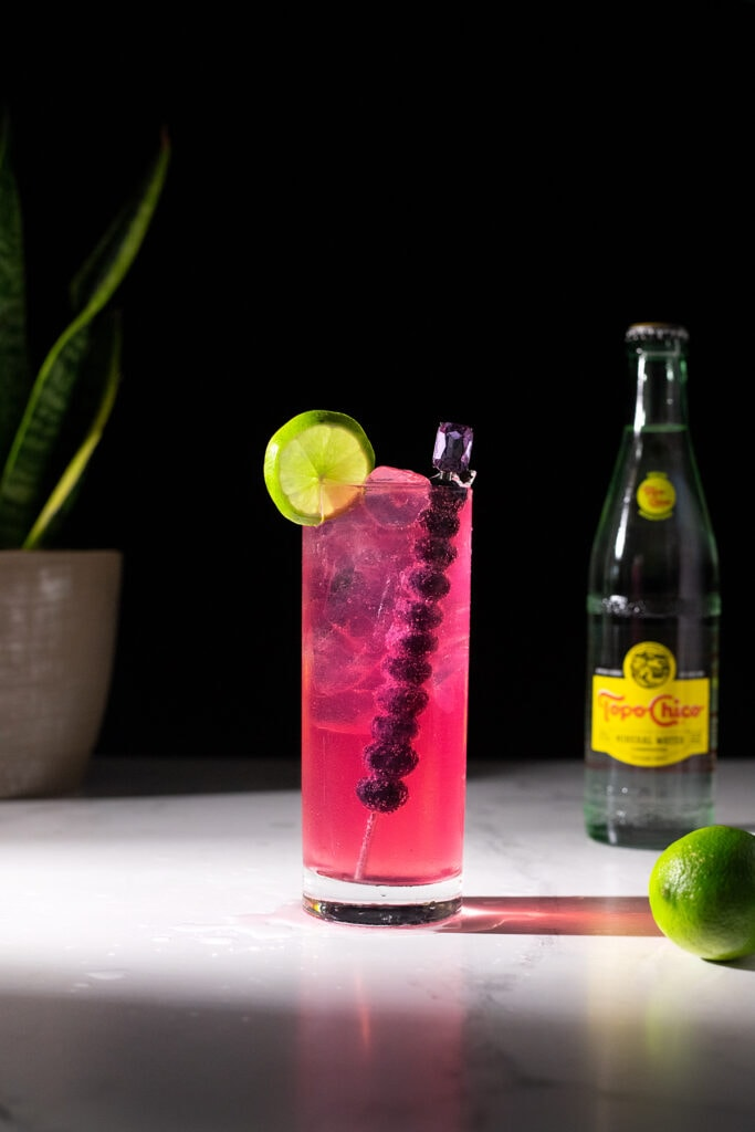 a bright pink highball next to a bottle of Topo Chico.