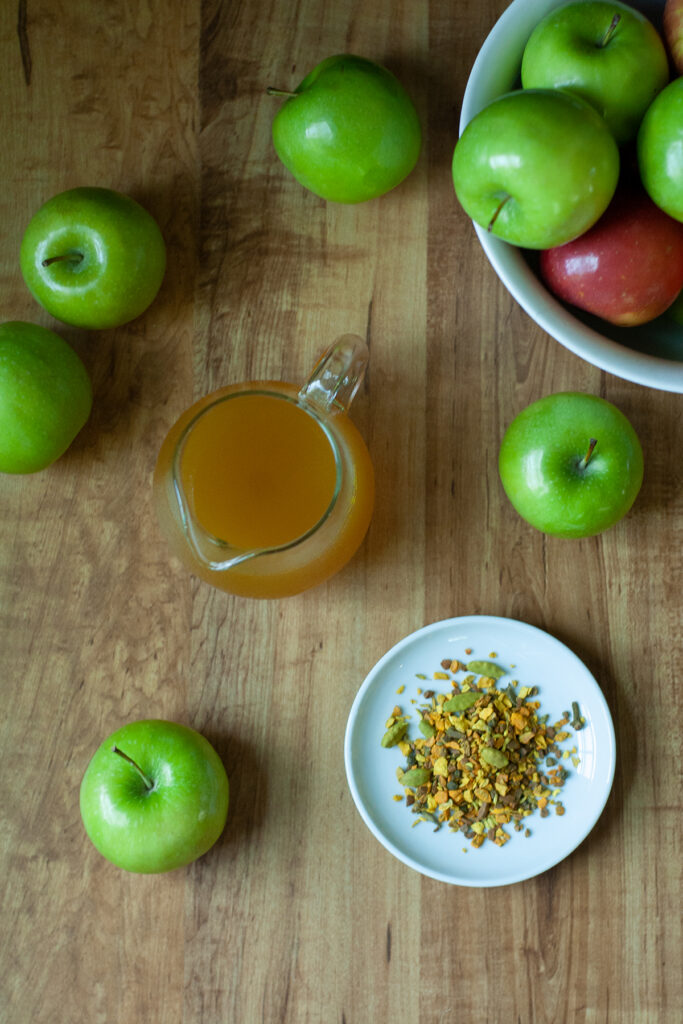 green apples on a wooden table with a pitcher of golden syrup and loose leaf tea.