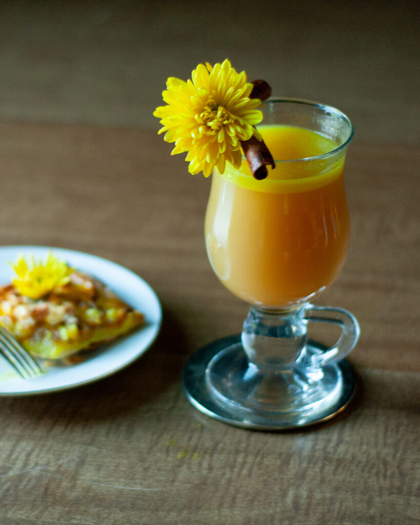 a glass of hot golden chai cocktail with a yellow flower.