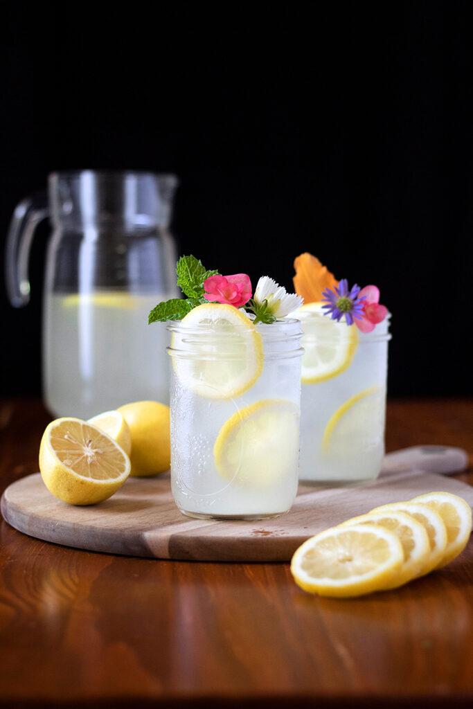 pitcher and mason jars of lemonade with lemon slices.