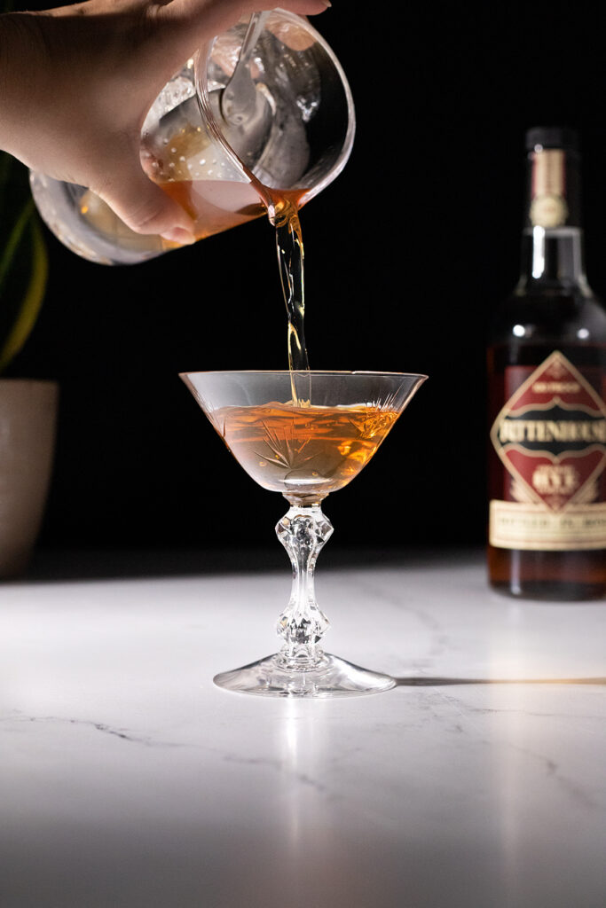 pouring a brown cocktail into a cocktail glass.