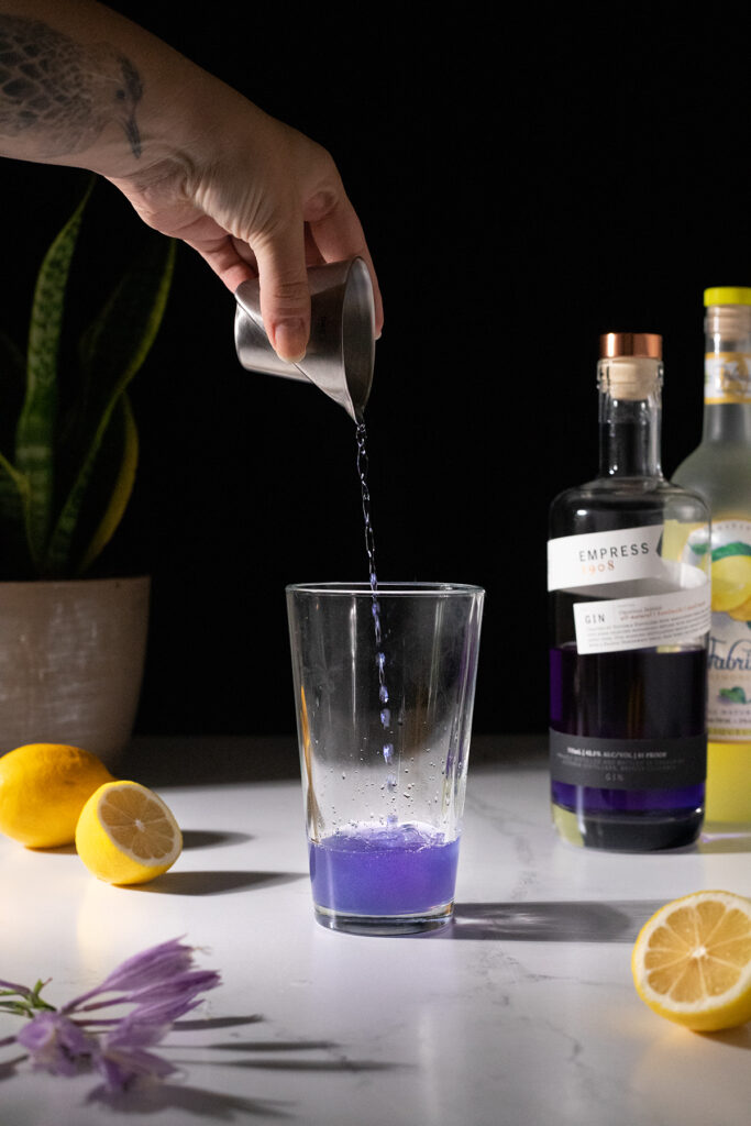 pouring purple Empress gin into a cocktail shaker.
