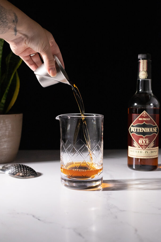 pouring whiskey into a mixing glass.