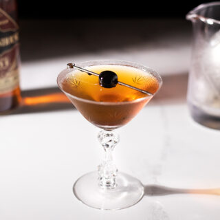 a vintage cocktail glass filled with a brown drink and a cherry on a pick.