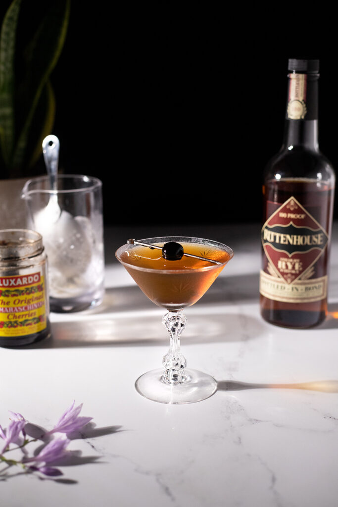 a brown cocktail next to a rye whiskey bottle and a mixing glass.