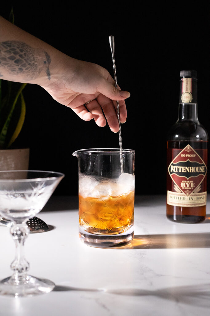 stirring a whiskey cocktail with ice and a long bar spoon.