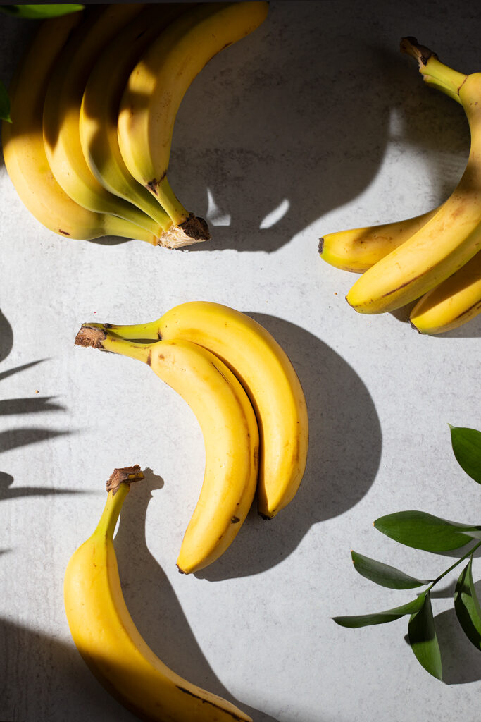 several bananas on a grey table with green leaves.
