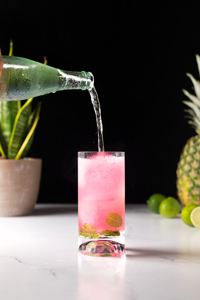 topping the pink coconut Mojito with sparkling water.