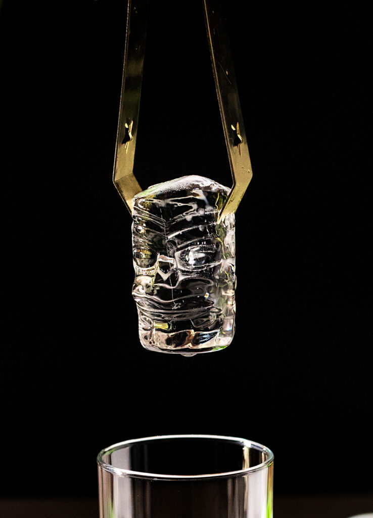 a clear ice cube shaped like a tiki head.