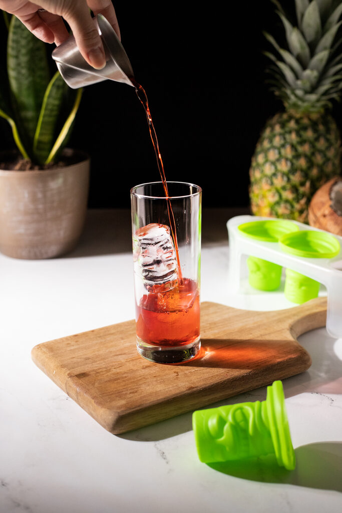 pouring red liqueur over clear tiki ice in a highball glass.