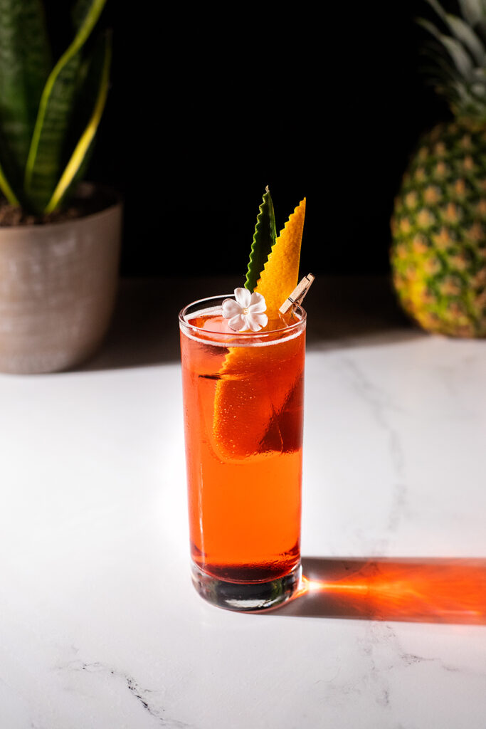 a tall, red drink garnished with a pineapple leaf and an orange peel cut into a leaf shape.