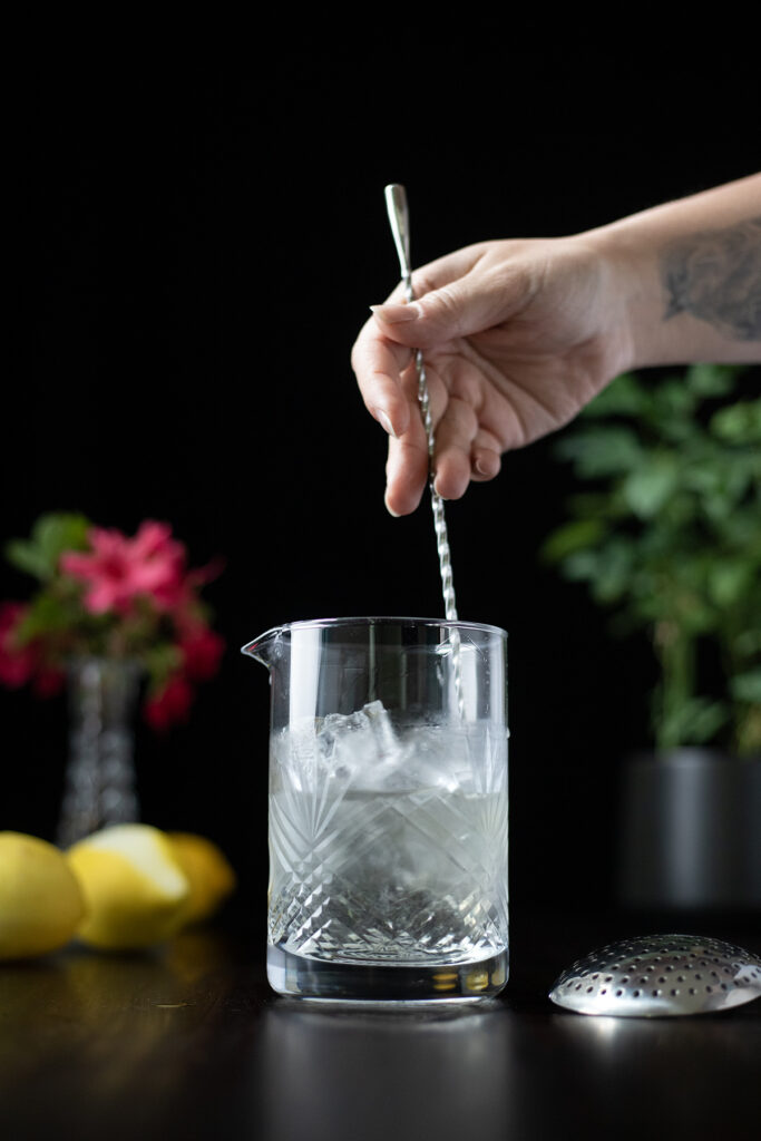 a hand stirring clear liquid and ice in a mixing glass with a bar spoon