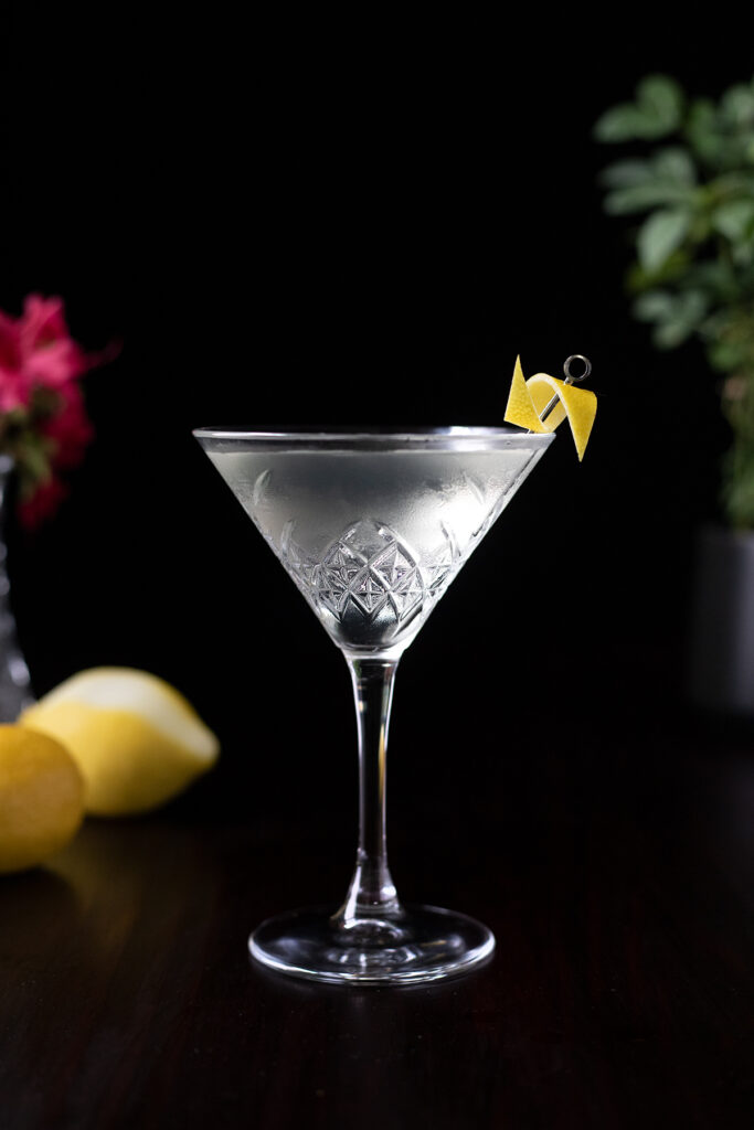 a martini next to lemons and flowers.
