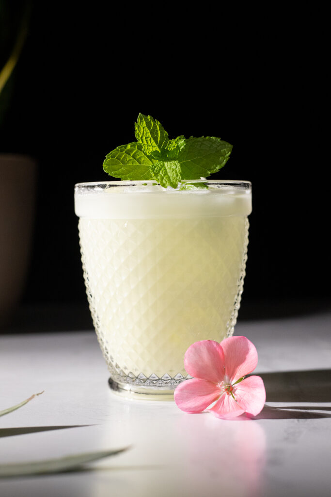 close up of white drink in lowball glass with mint.