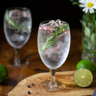 a goblet filled with a clear, bubbly drink, rosemary and pink peppercorns.