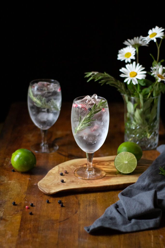 two gin and tonics in large goblets on a wooden cutting board.