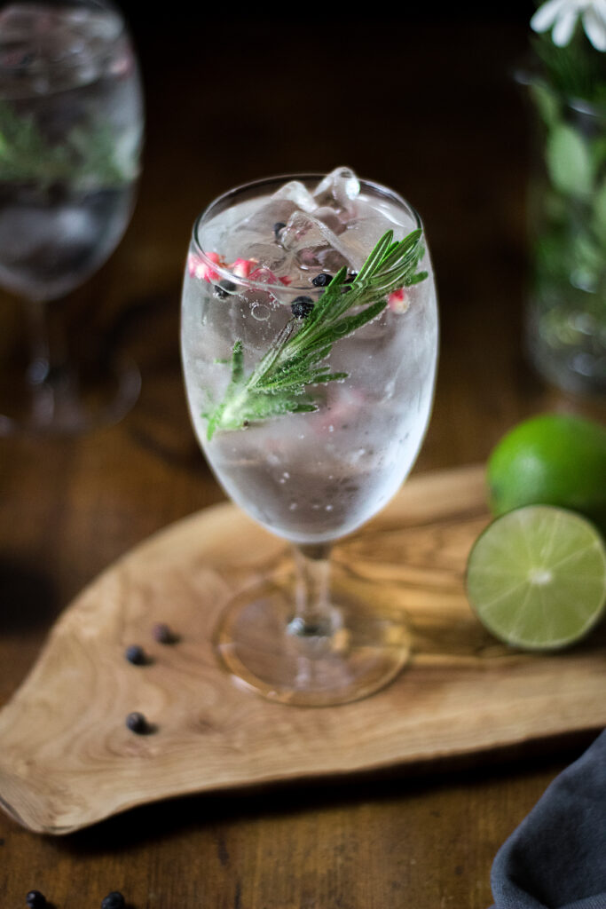 a close up of rosemary and pink peppercorns in a glass of gin and tonic.