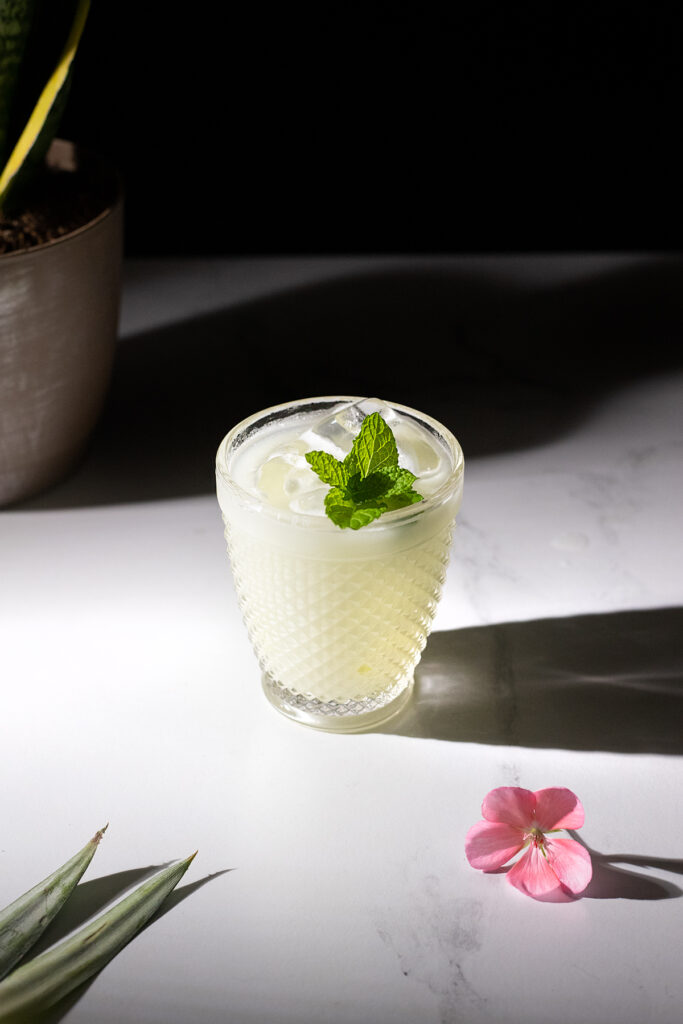 pina verde in a rocks glass with mint and a flower.