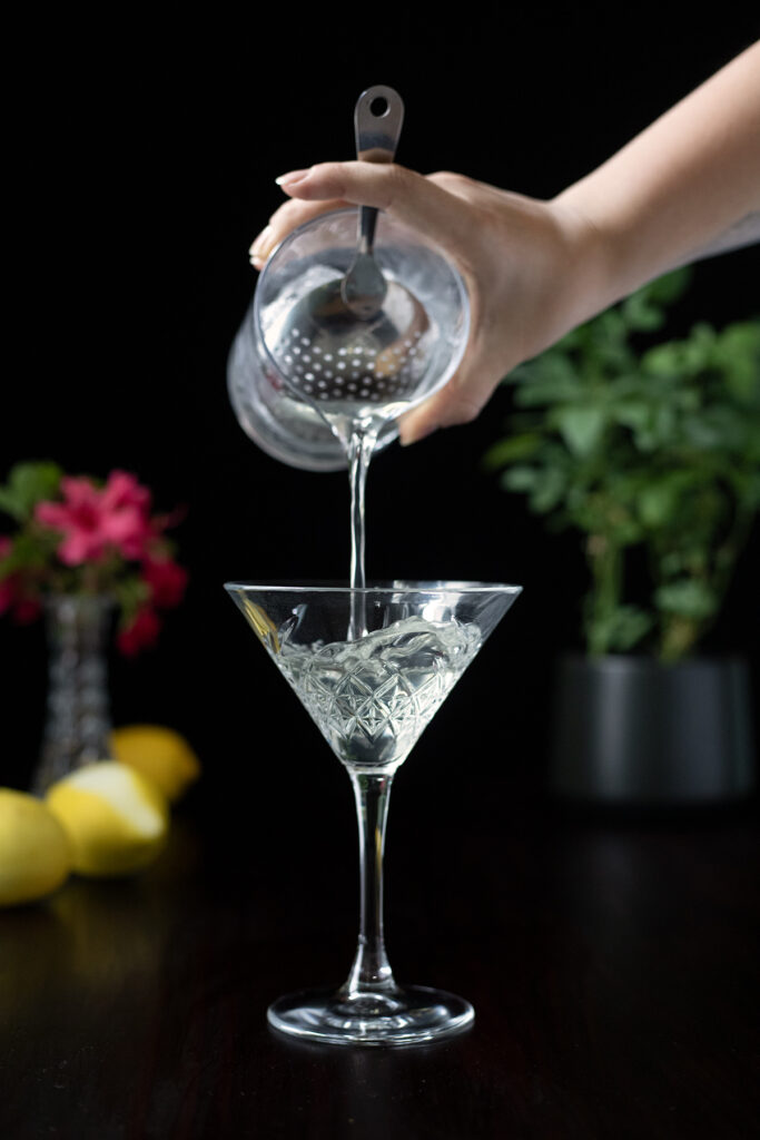 pouring a martini into a cocktail glass
