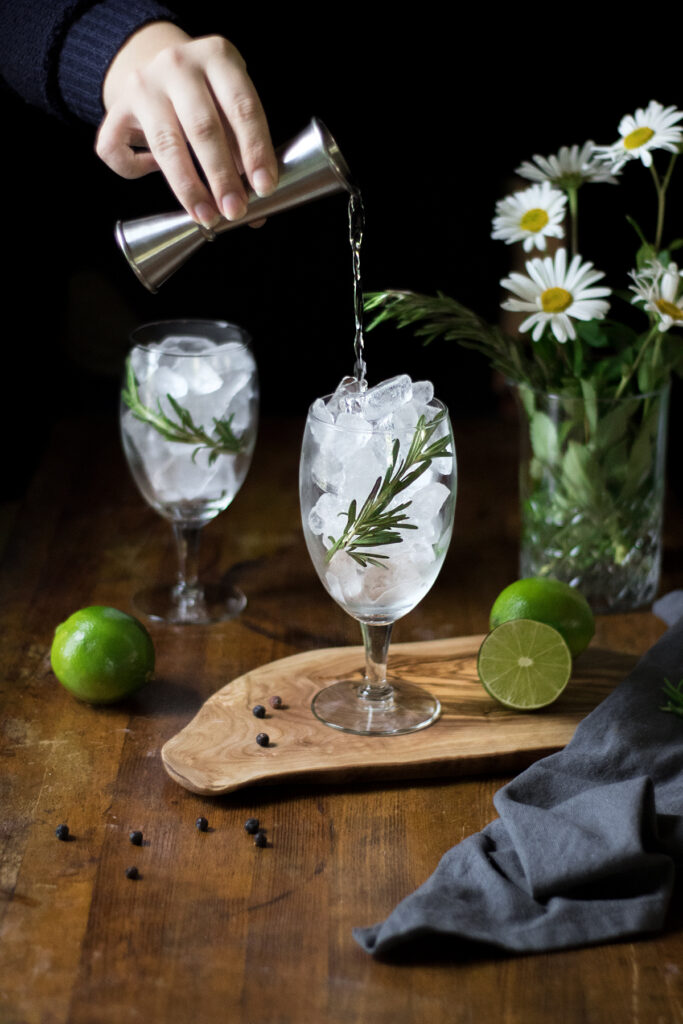pouring gin from a jigger into a glass full of ice.