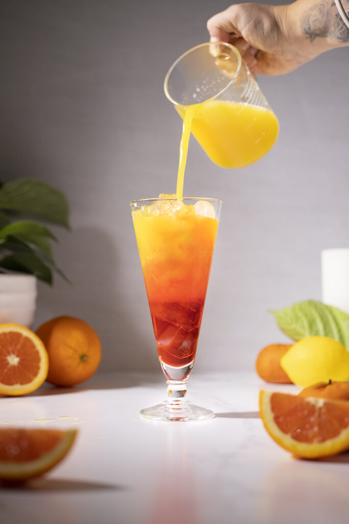pouring orange juice from a pitcher into a red drink.