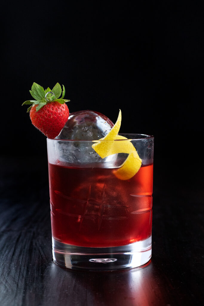 a bright red drink in a rocks glass with a strawberry and a lemon twist.
