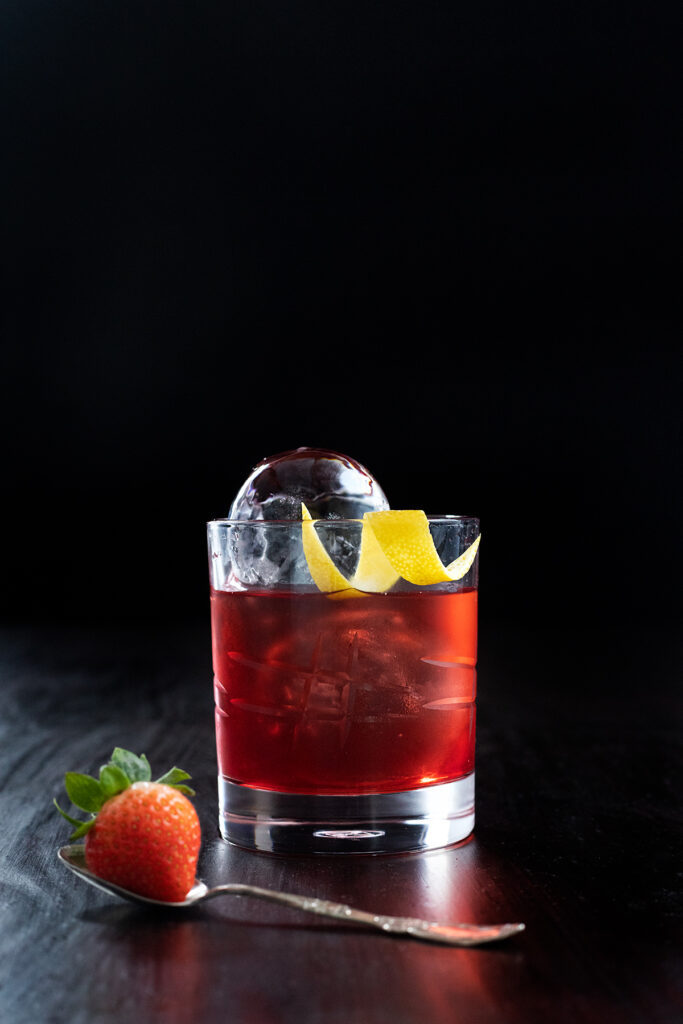 a red drink with clear ice spheres in a rocks glass.