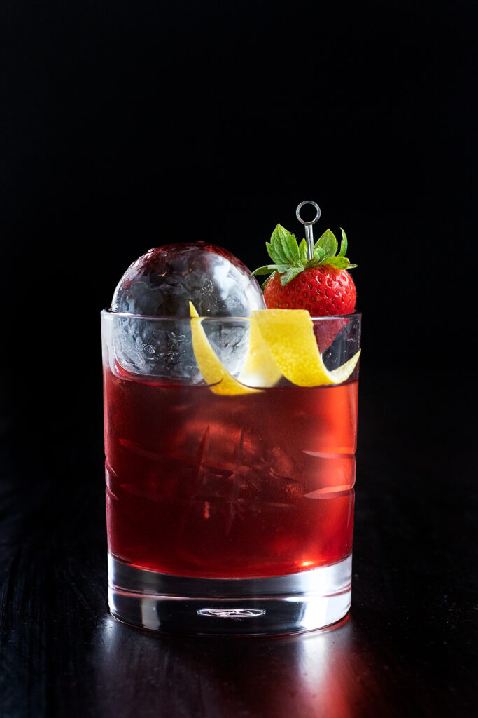 a red drink with a strawberry on a cocktail pick.