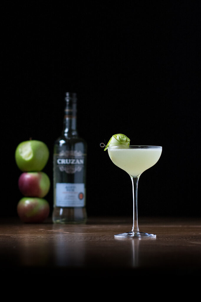 a cocktail in a coupe glass next to a bottle of white rum and three stacked apples.