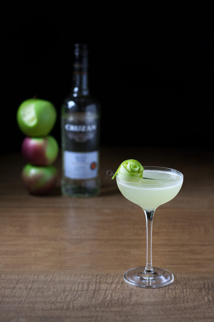 a pale green cocktail next to a bottle of Cruzan white rum and three apples.