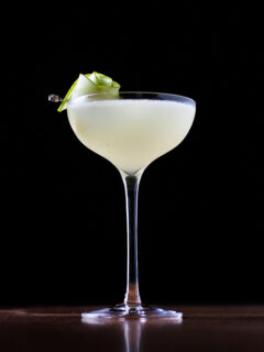 a pale yellow cocktail in a tall coupe glass with a rose garnish made from green apple slices.