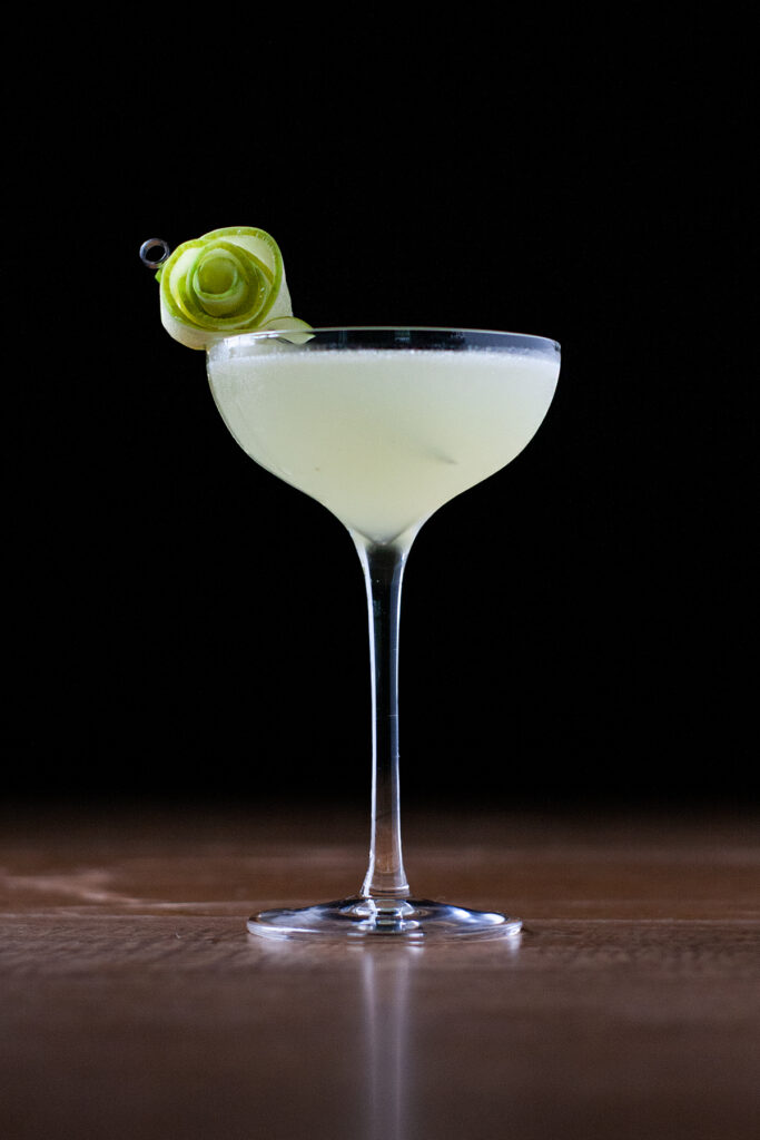 a pale green cocktail in a coupe glass garnished with a rose made from green apple slices.