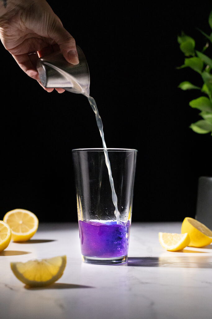 pouring lemon juice into Empress Gin, making it turn from blue to pink.