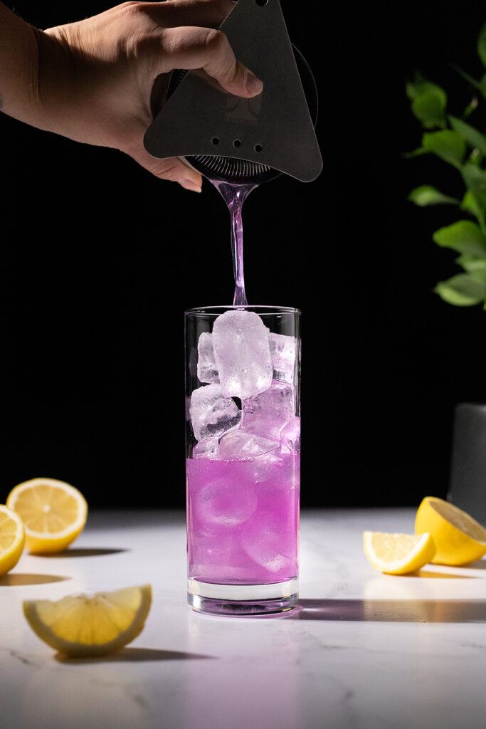 straining a purple cocktail into a tall glass filled with ice.