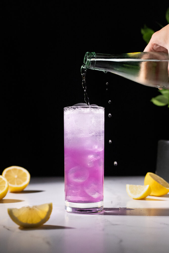 pouring carbonated water into a pink drink in a tall glass.