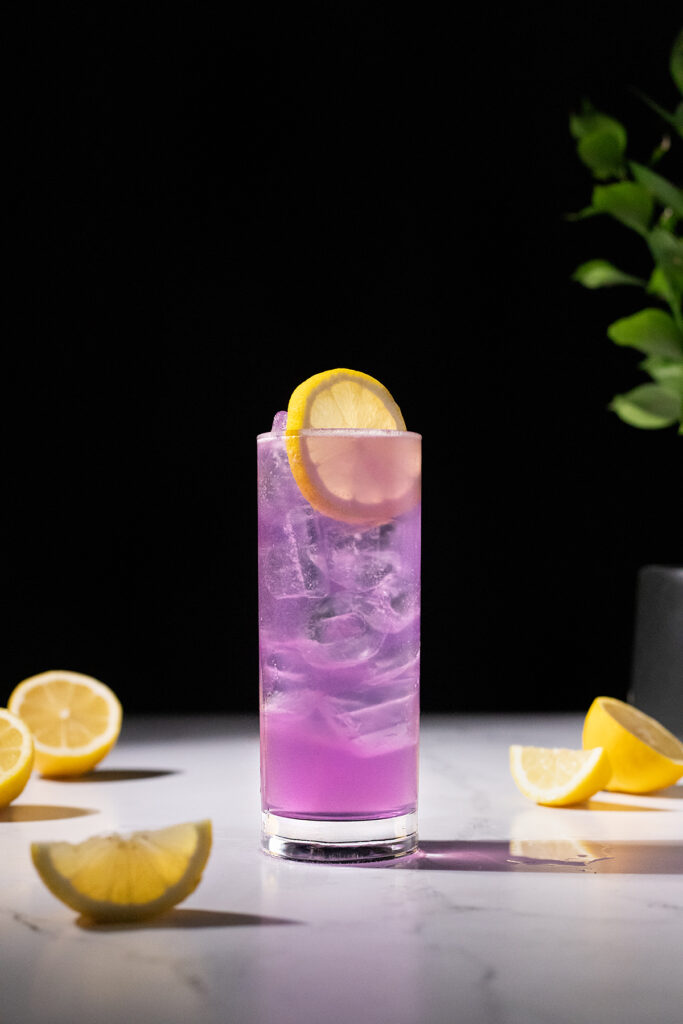 a tall purple drink garnished with a lemon wheel.